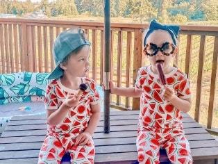 two kids eating snacks on KidKraft outdoor table