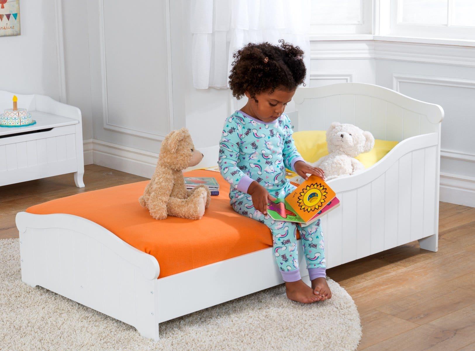 Girl sitting on toddler bed