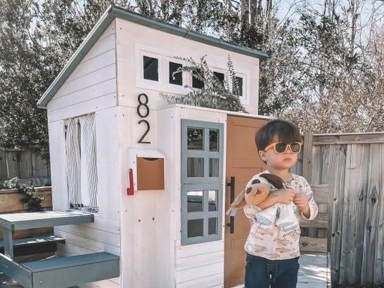 White modern playhouse with boy holding stuffed animal