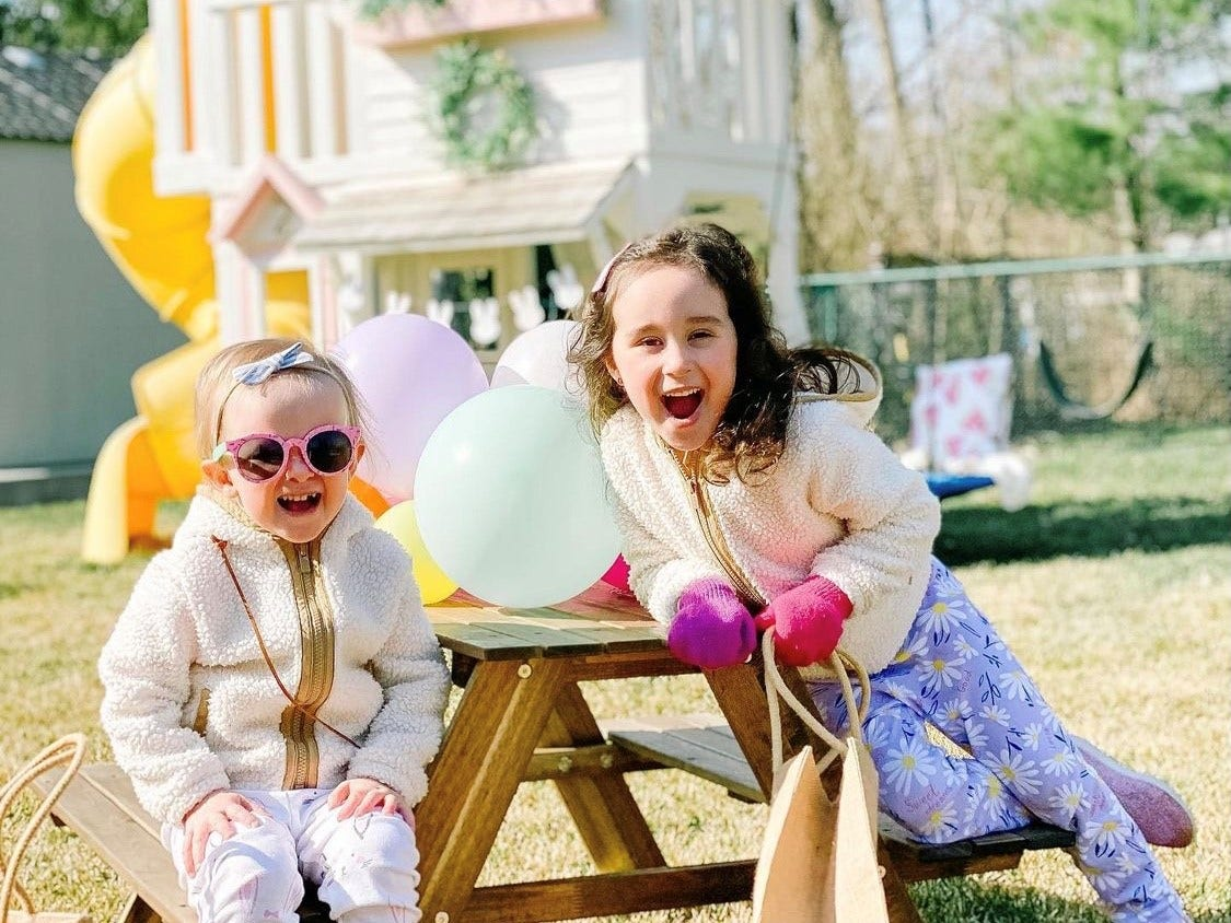 two girls sitting on outdoor table with KidKraft swingset in the background