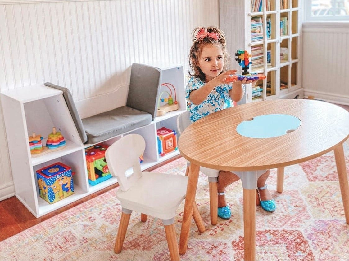 Girl sitting at KidKraft table with reading nook in the background