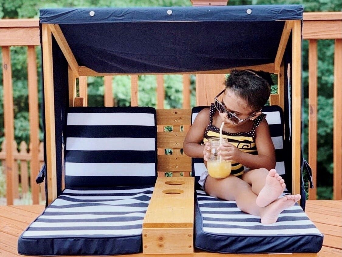 girl sitting on kids lounge chair sipping a drink