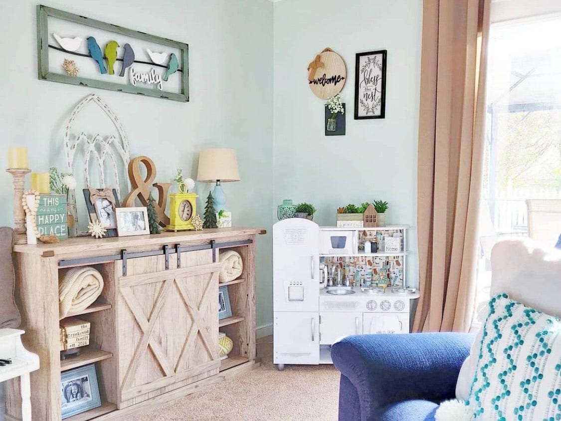 living room with green accents and white play kitchen