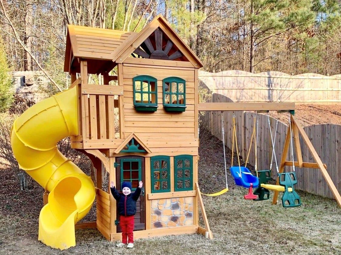 KidKraft swingset in backyard with child smiling